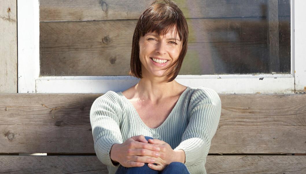 Kvinna sitter mot en trävägg och ser glad ut.