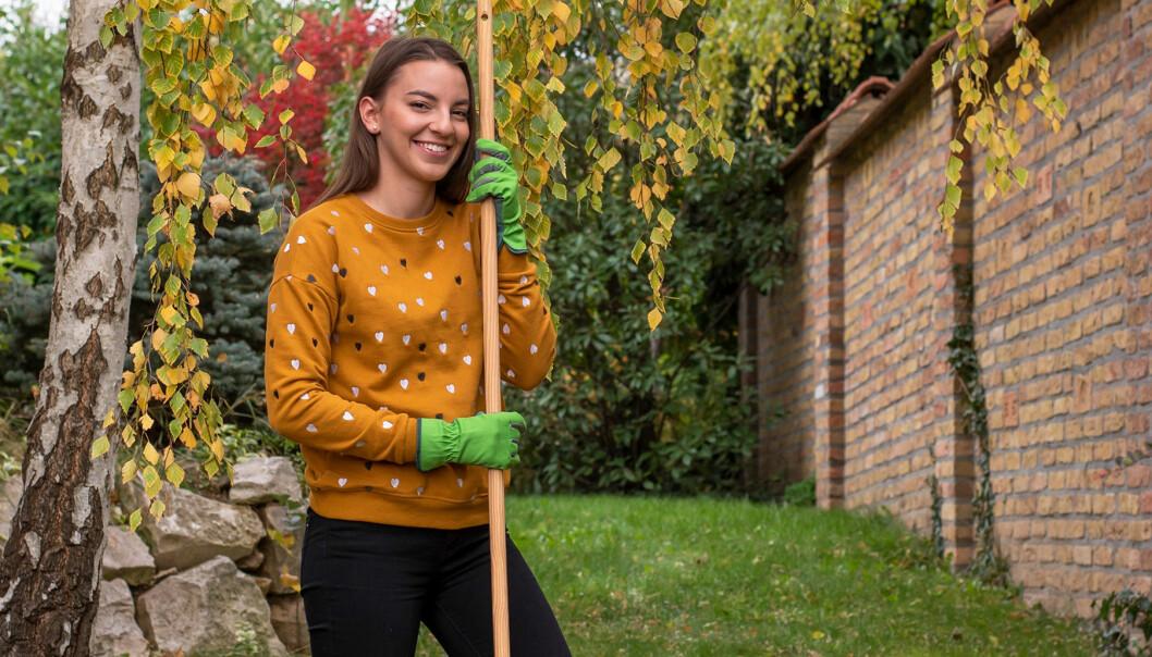 Kvinna står med räfsa i handen och gör trädgården redo för vintern