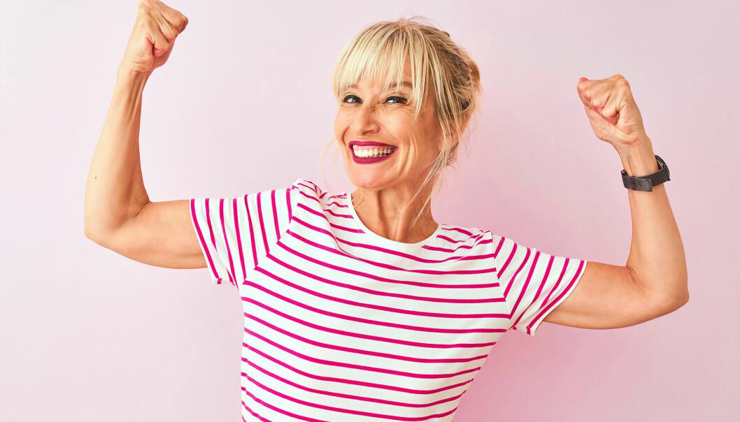 Leende kvinna spänner musklerna