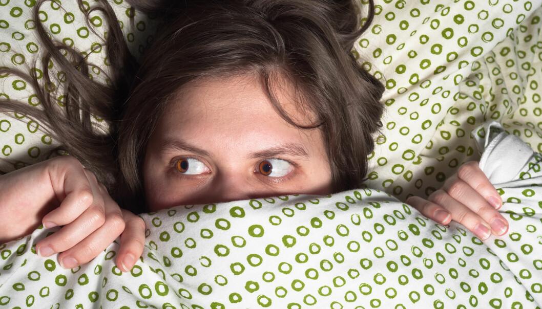 Kvinna gömmer sig under täcke