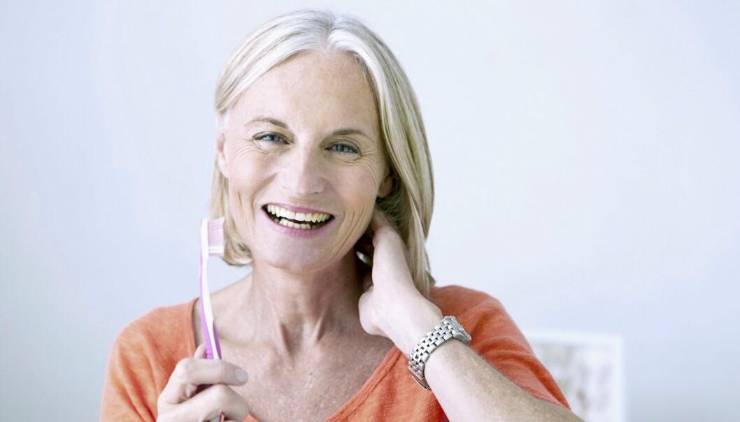 Glad kvinna håller en tandborste i handen