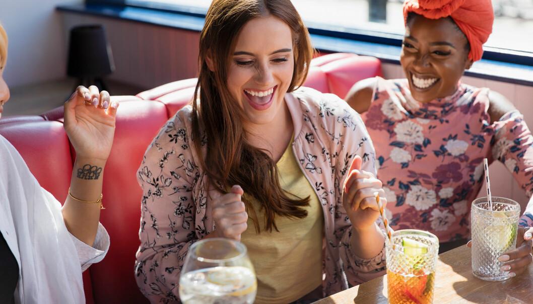 Tre glada kvinnor firar in helgen med en drink