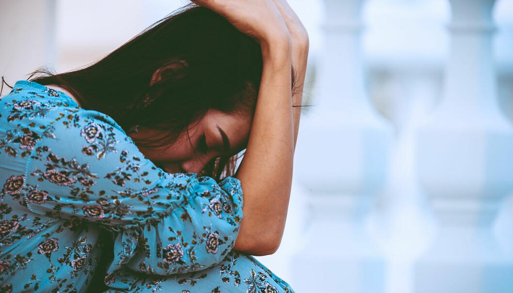 Ledsen och sviken kvinna gråter med ansiktet i armarna