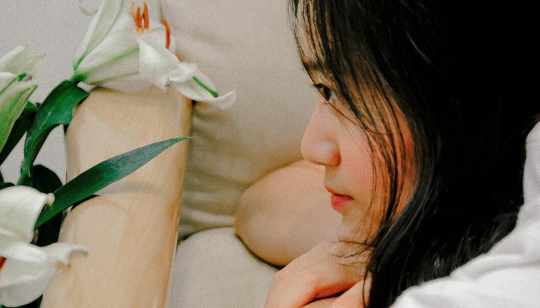 Kvinna ligger i en soffa och ser nedstämd ut.