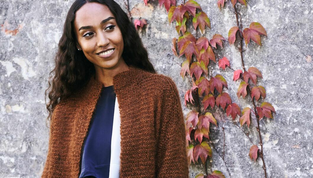 Porträtt av en ung kvinna iklädd en rätstickag kofta i lite längre modell