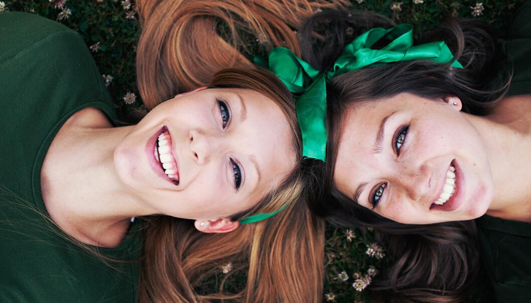 Två systrar ligger ner och tittar in i kameran