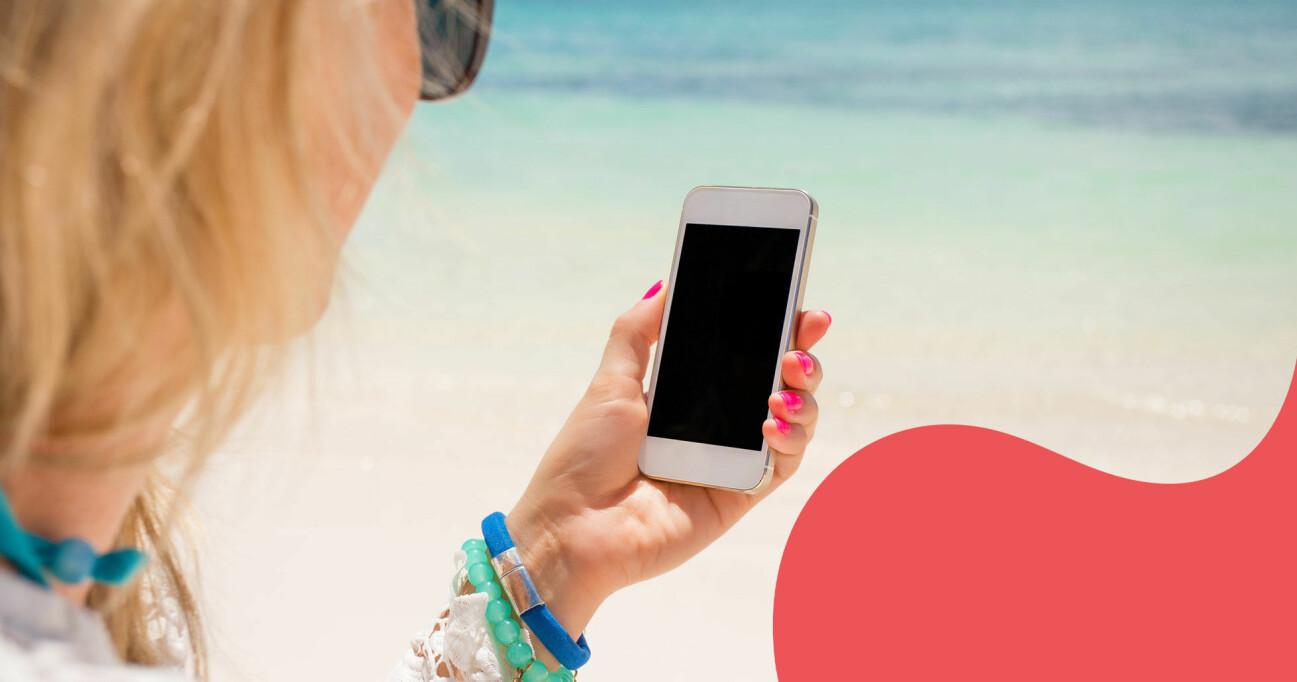 Kvinna på stranden med smartphone.