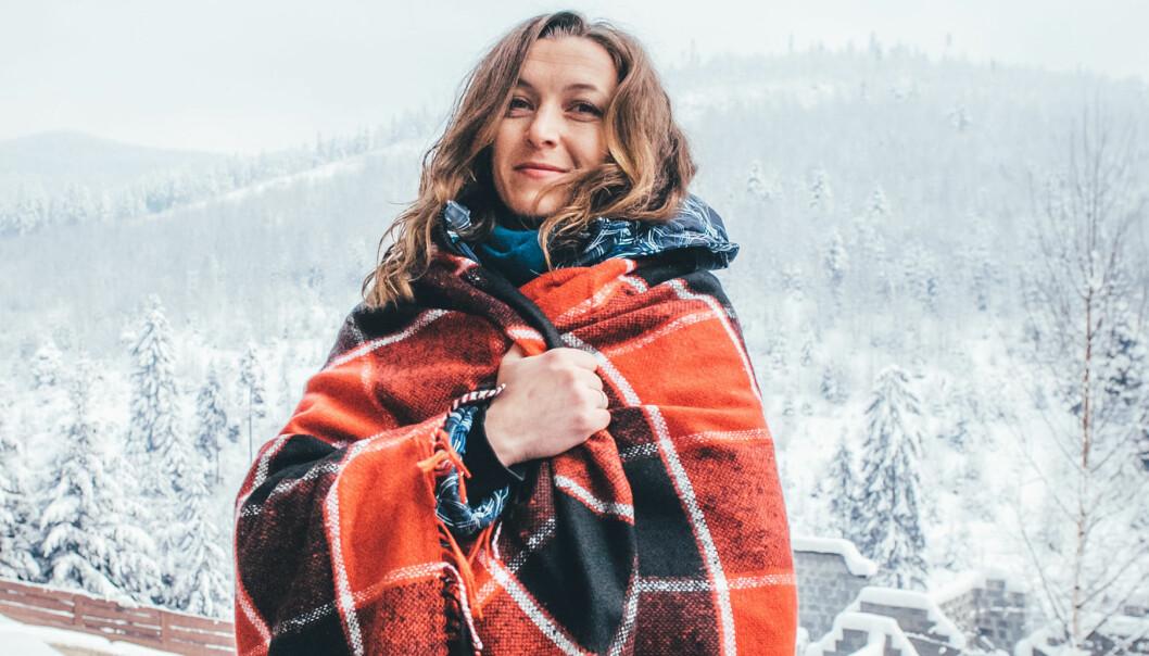 Kvinna invirad i filt med vinterlandskap i bakgrunden.
