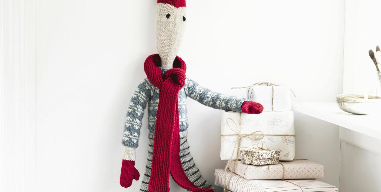 Detaljbild av stickad jultomte som är fäst på väggen och håller armen på en hög julklappar.