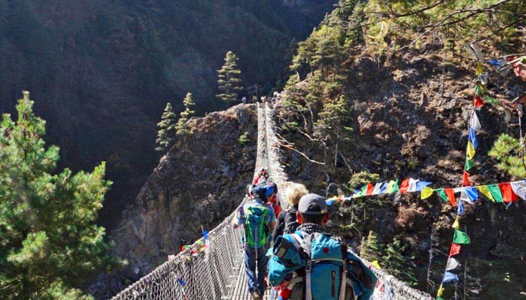 Människor klättrar över en hängbro i Nepal.