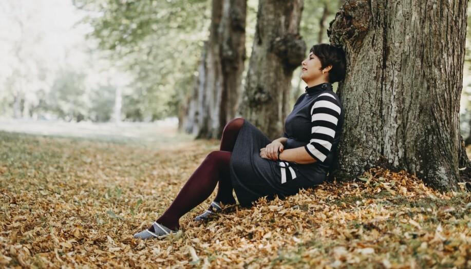 Andréa, som drabbades av tyst hjärtinfarkt, sitter vid ett träd och återhämtar sig.