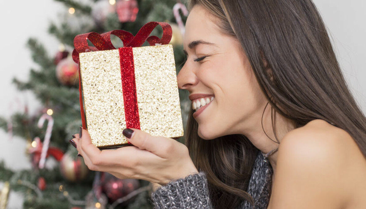 Kvinna tittar på en julklapp och ler stort