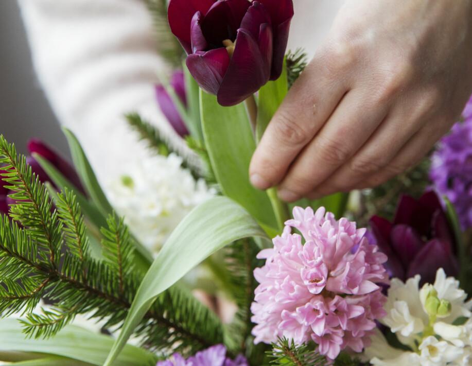 Maffig blomsterbukett av hyacinter, tulpaner och kvistar från barrträd.