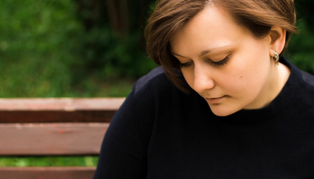 Kvinna ser ledsen och ensam ut.