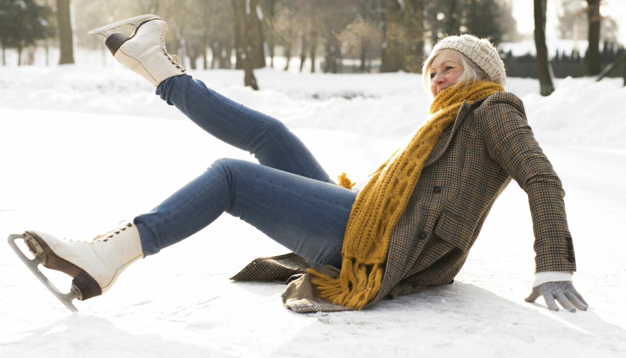 Kvinna som halkat ligger på isen.