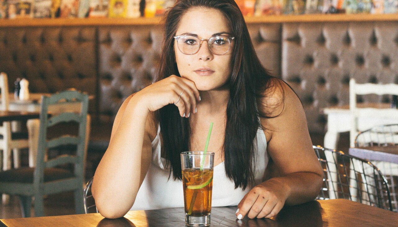 Kvinna sitter på ett kafé och dricker iste.