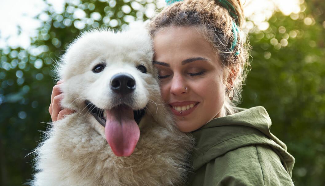 Kvinna håller om sin hund på ett kärleksfullt sätt.