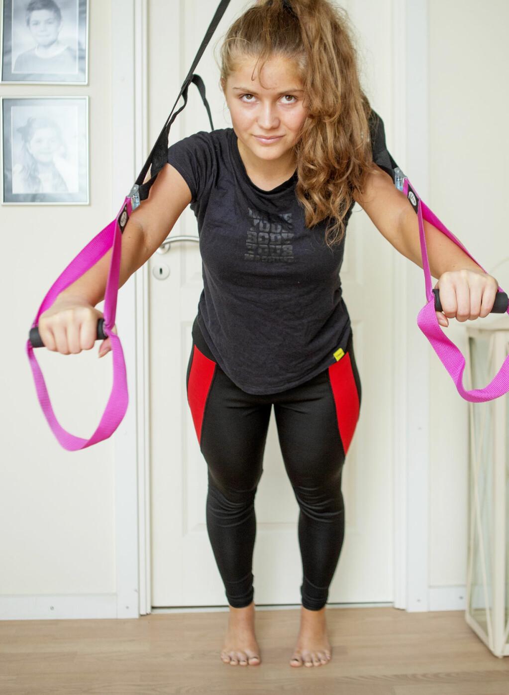 Sacha i träningskläder tränar muskler med styrkeband i hemmet.