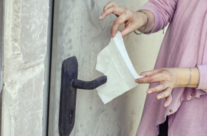 Kvinna torkar ett dörrhandtag med en servett.
