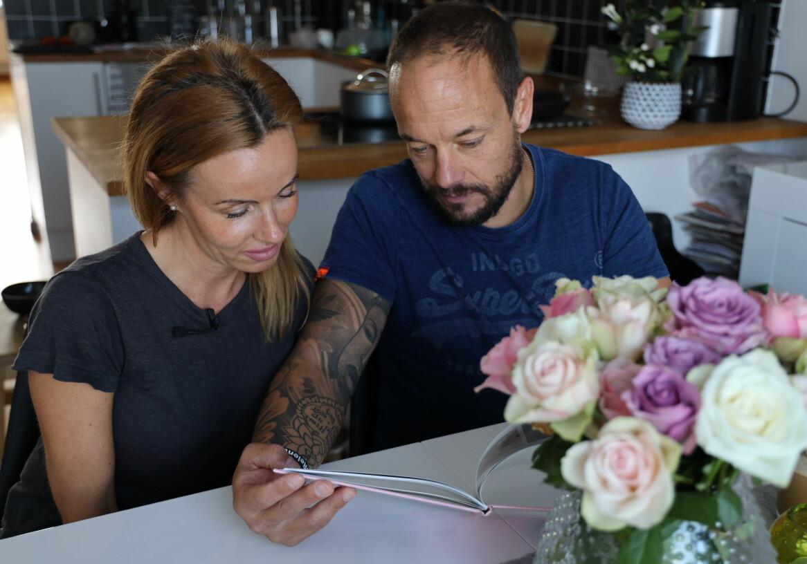 Emma Aldin och Rickard Lundqvsit tittar i ett fotoalbum i lägenheten i Malmö.