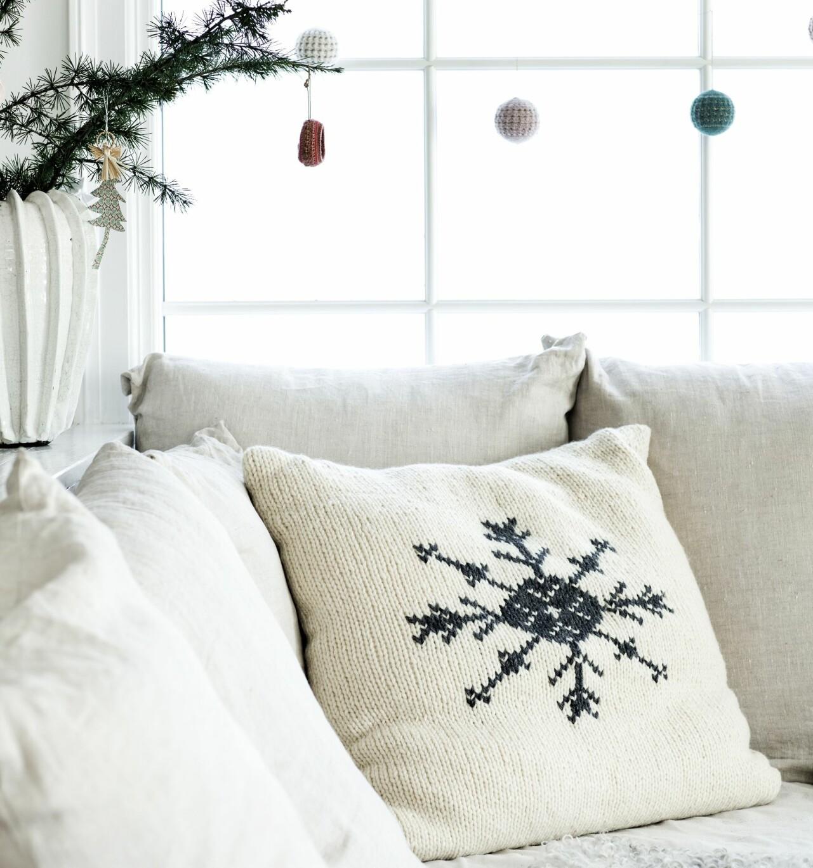 Kudde med broderat mönster av snöflinga i soffa.