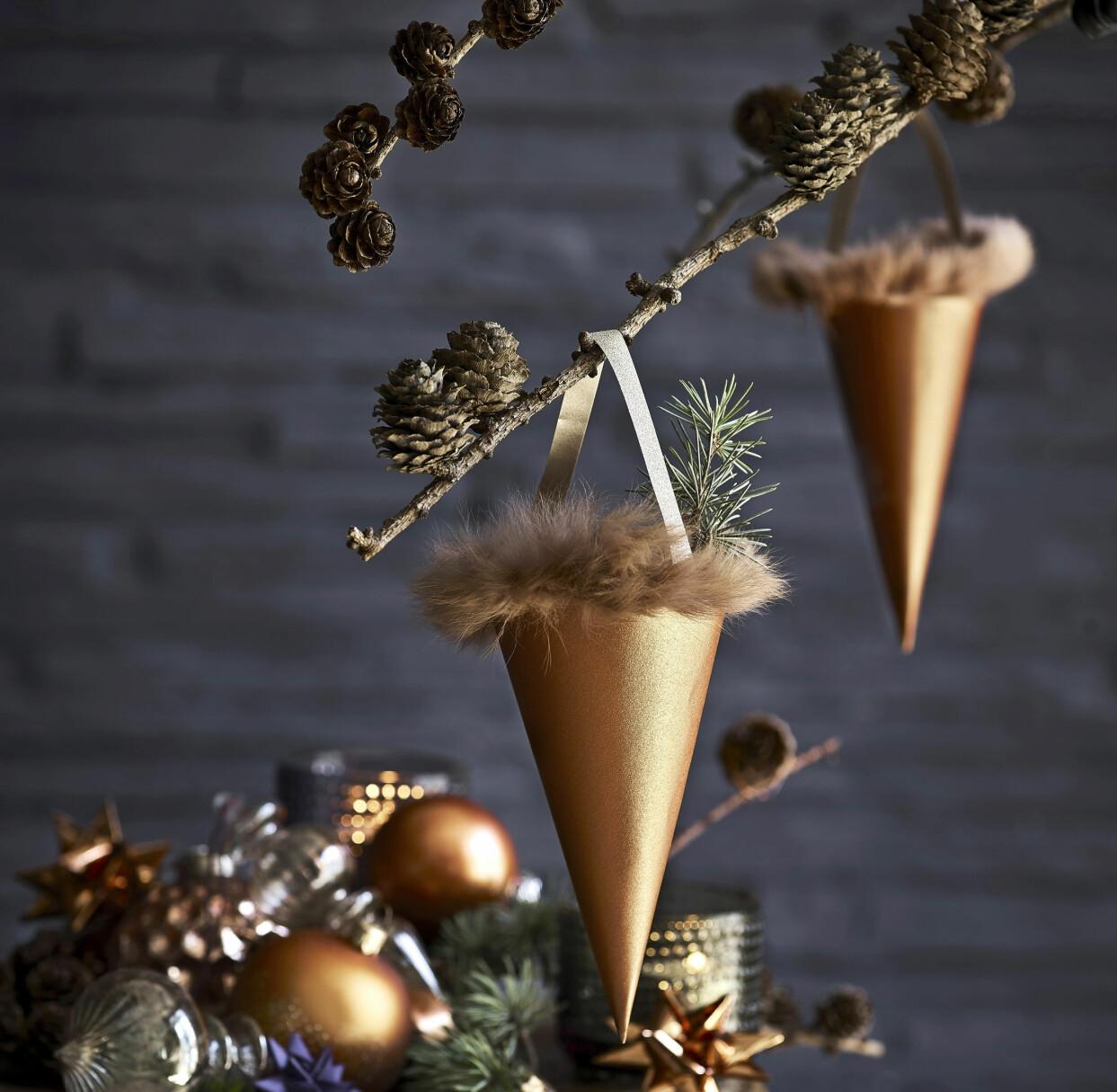 Hemgjorda pappersstrutar med pälskant upphängda i en gren med kottar.