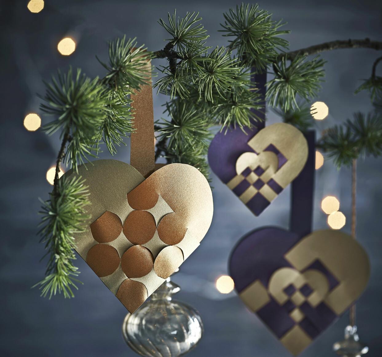 Flätade pappershjärtan som hänger i en kvist från en julgran.