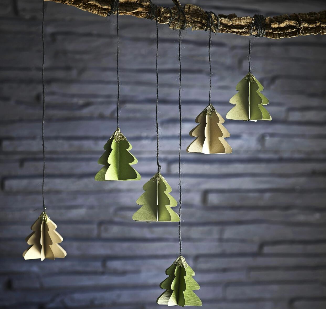 Hemgjorda pappersgranar med glitter upphängda i snören.