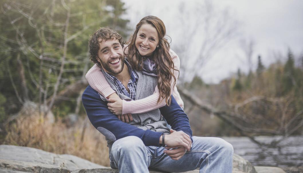 Kvinna och man ler och håller om varandra.