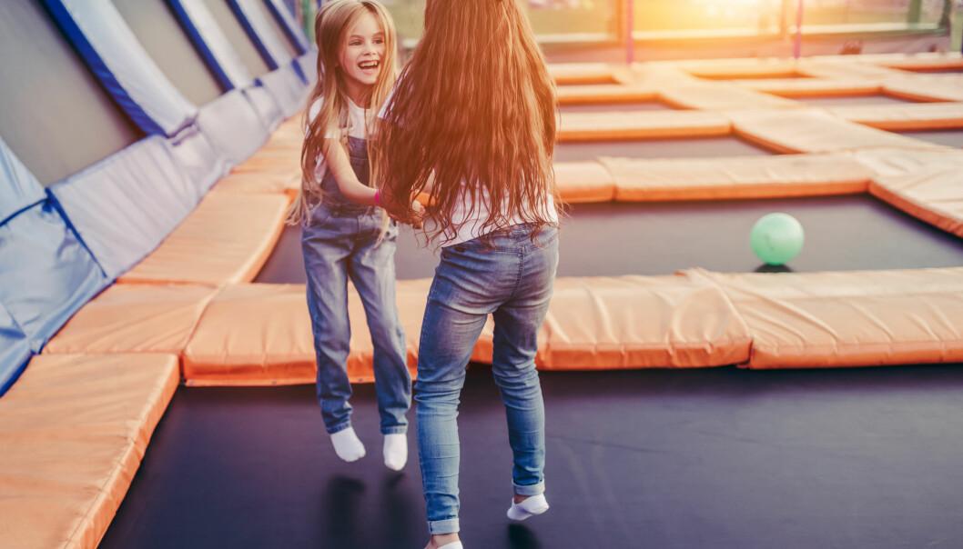 Två flickor hoppar och leker i en trampolinpark.