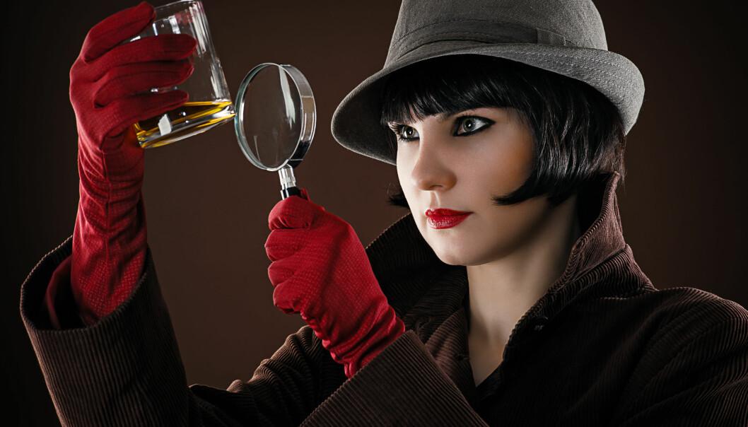 En kvinnlig detektiv undersöker ett glas med förstoringsglas.