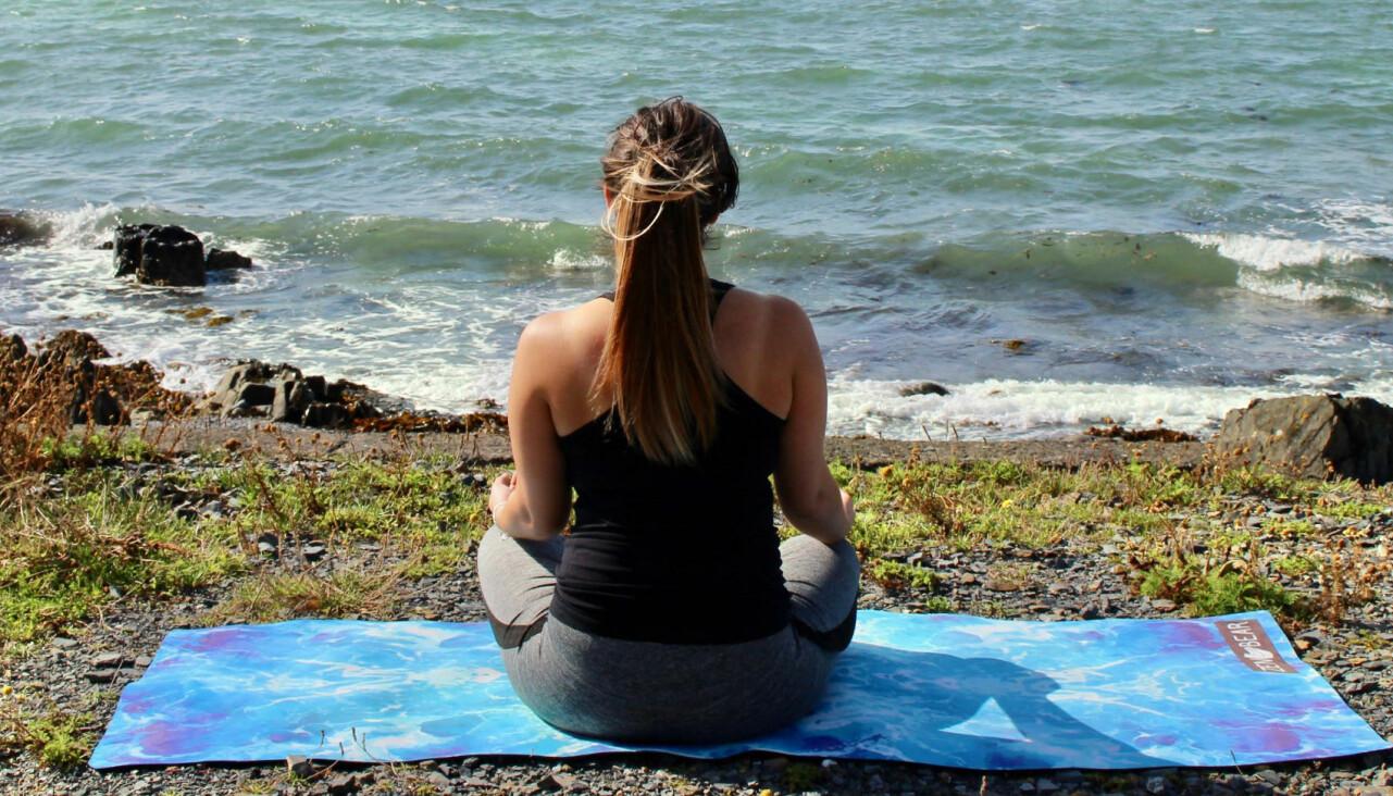 Kvinna sitter vid havet och tränar yoga.