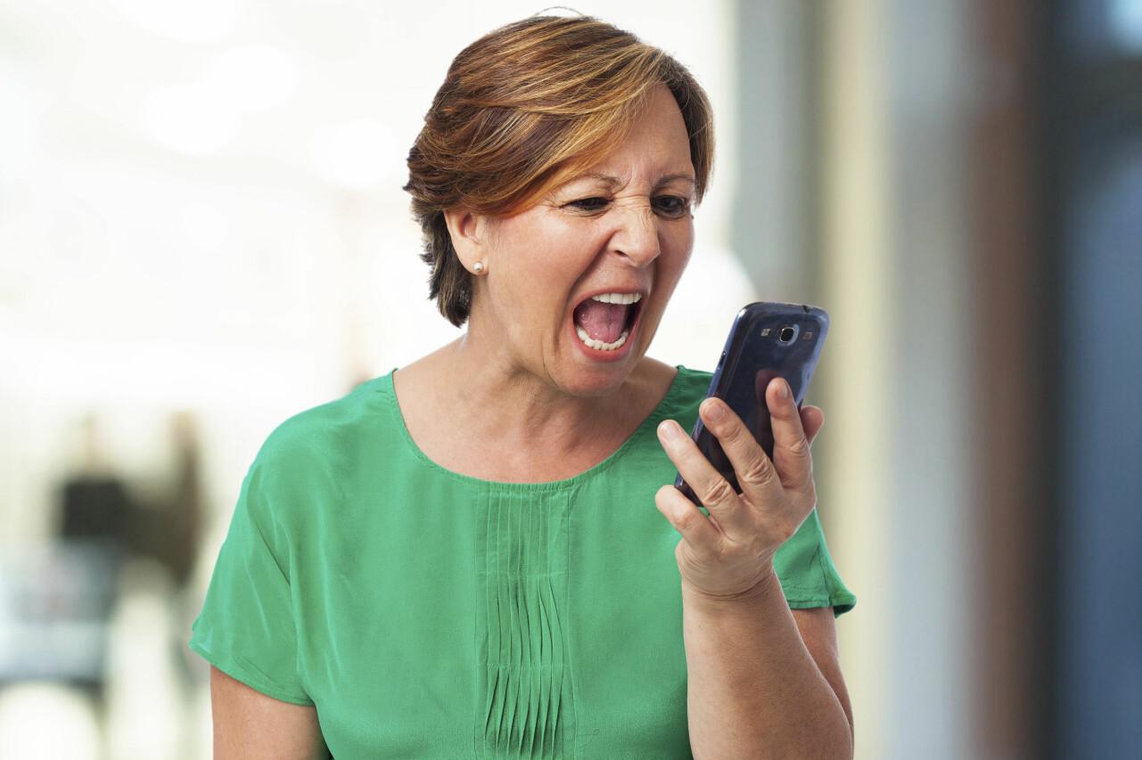 Arg kvinna skriker på sin telefon.