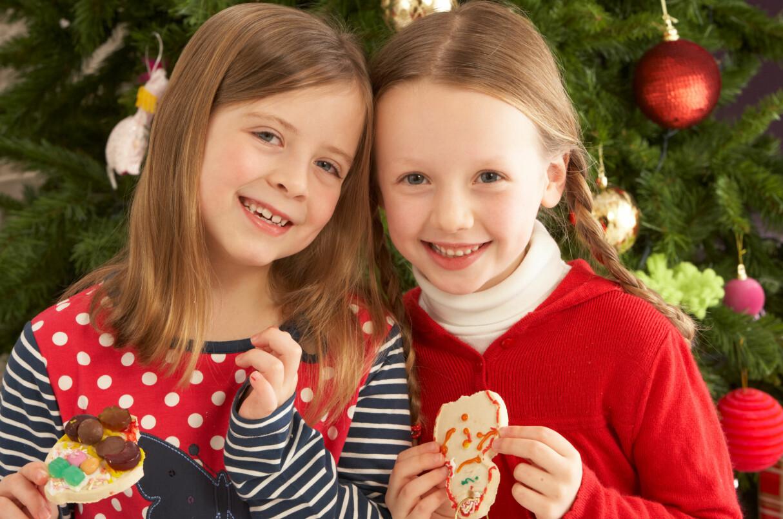 Två systrar, sju år, framför julgranen.
