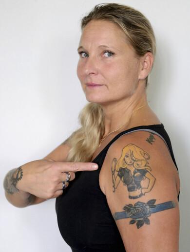 Polisen Jenny, som misshandlades av sin partner, pekar på en tatuering av en stark kvinna.