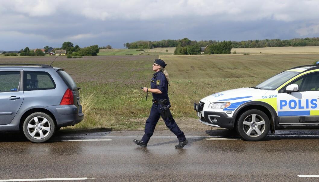 Polisen Jenny Svenningsson promenerar mellan två bilar.