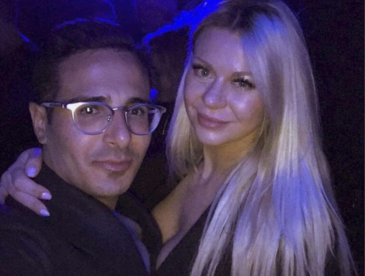 Pernilla tillsammans med Simon Leviev i en nattklubbsliknande miljö.