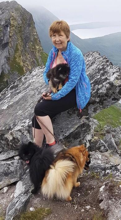 Venke sitter på en bergsklippa med sina tre hundar.