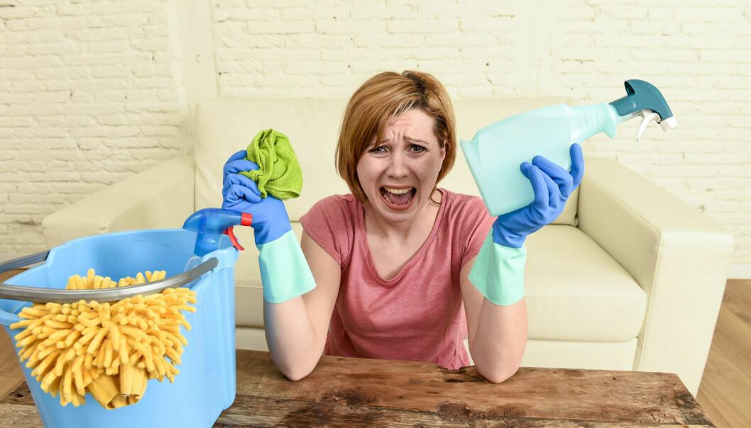 Kvinna håller städprodukter i handen och ser stressad ut.