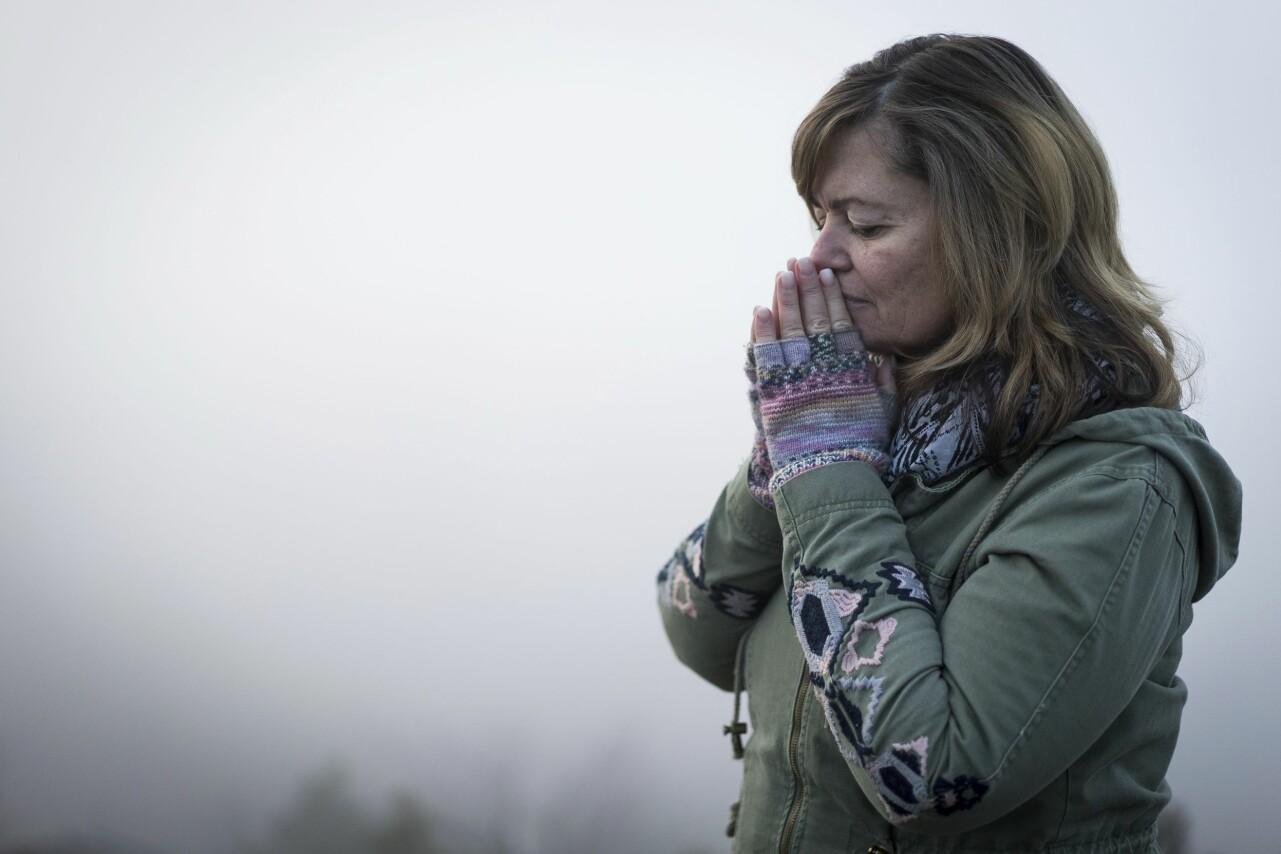En kvinna i övre medelåldern står med varm jacka och blundar eftertänksamt.