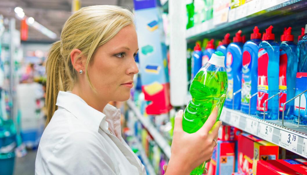 Kvinna tittar på rengöringsprylar i en butik.