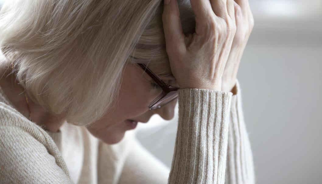 Kvinna sitter med huvudet i händerna efter en panikångestattack.