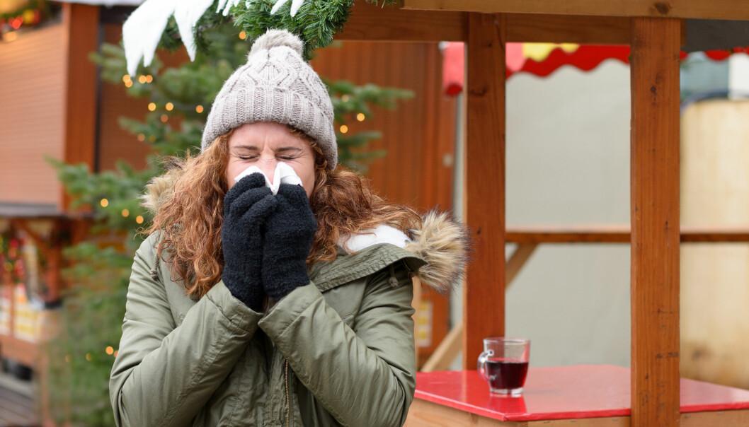 Kvinna nyser och snyter sig. I bakgrunden syns julpynt.