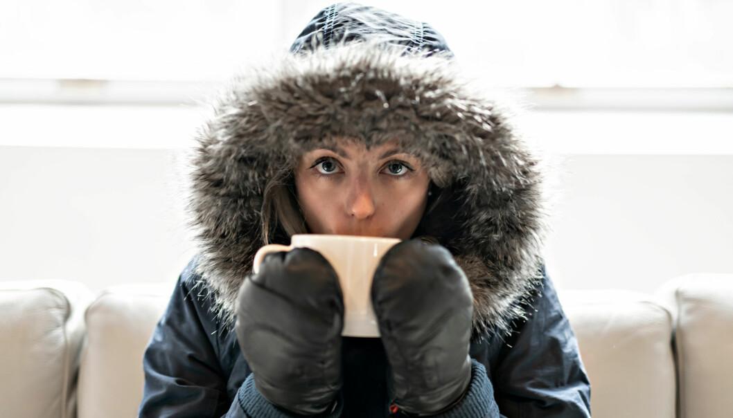Frusen kvinna i vinterjacka dricker kaffe i soffan.