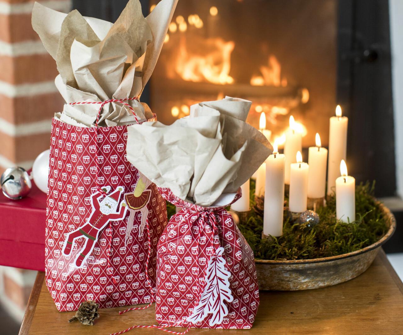 Julklappar inslagna i hemgjorda presentpåsar av papper.