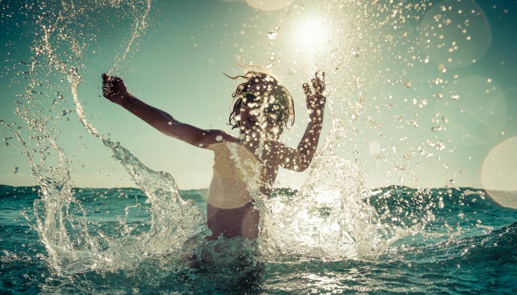 Barn badar och leker i havet.