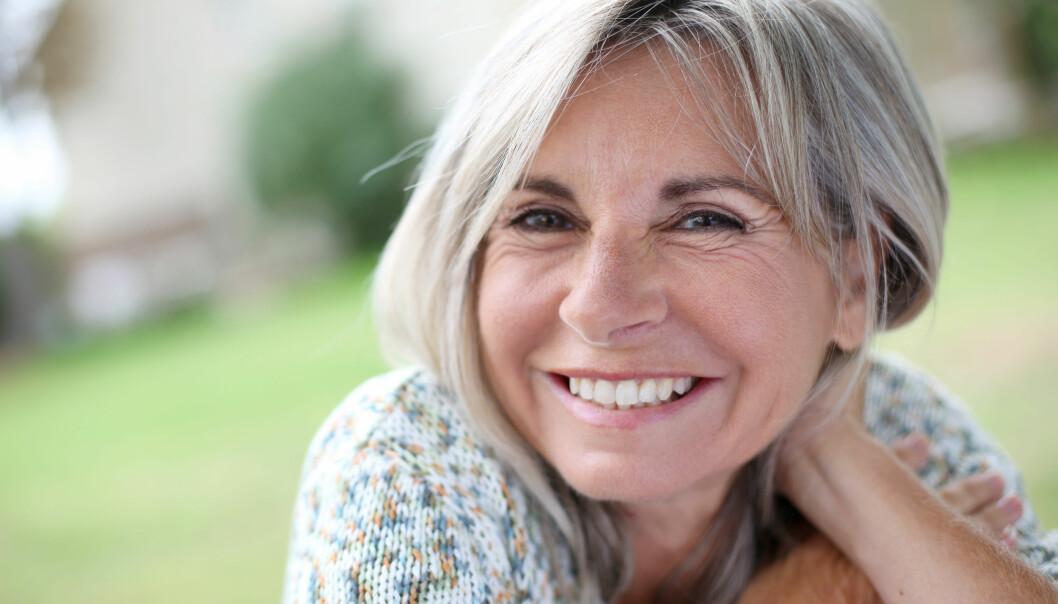 Medelålders glad kvinna ler