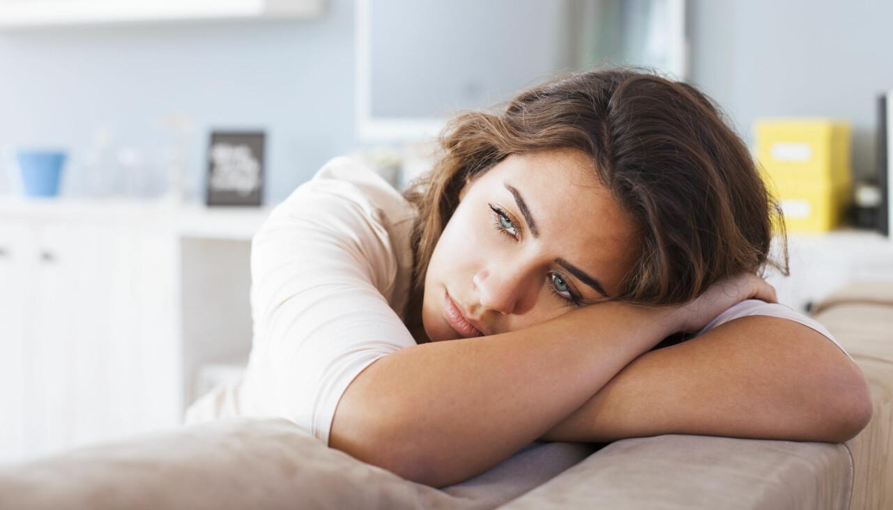 Kvinna ligger på en soffa och ser fundersam och stressad ut.