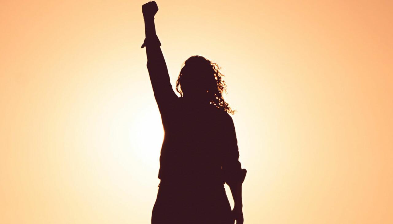 Kvinna höjer knuten näve i luften.