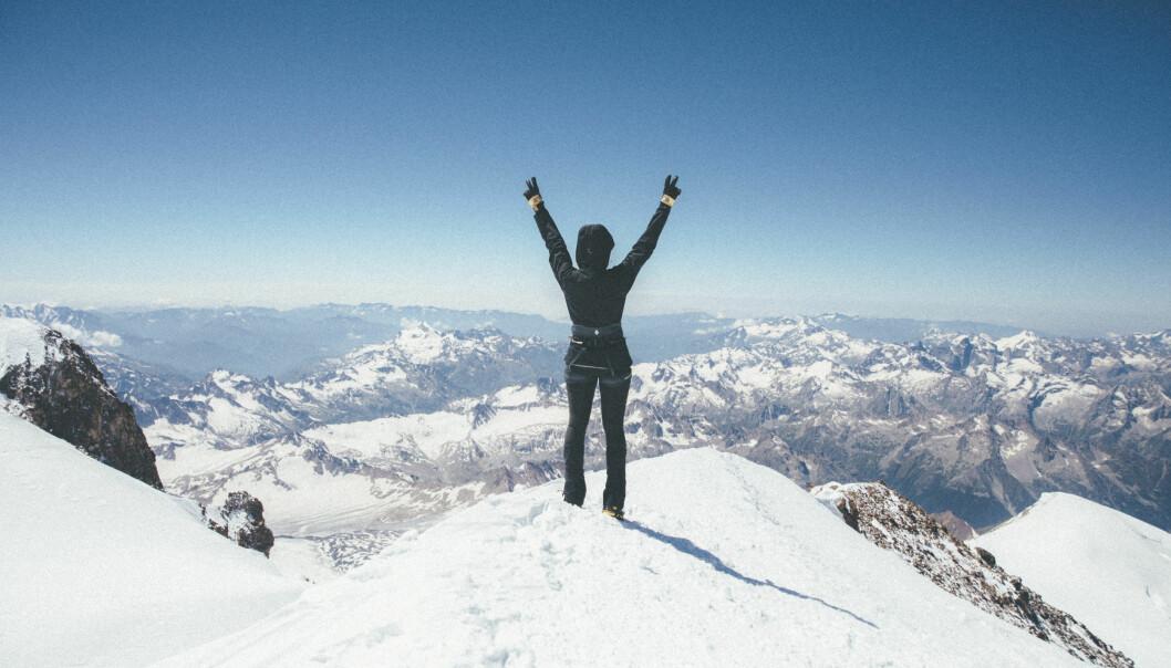 Emma sträcker upp armarna mot himlen där hon står på toppen av ett berg.